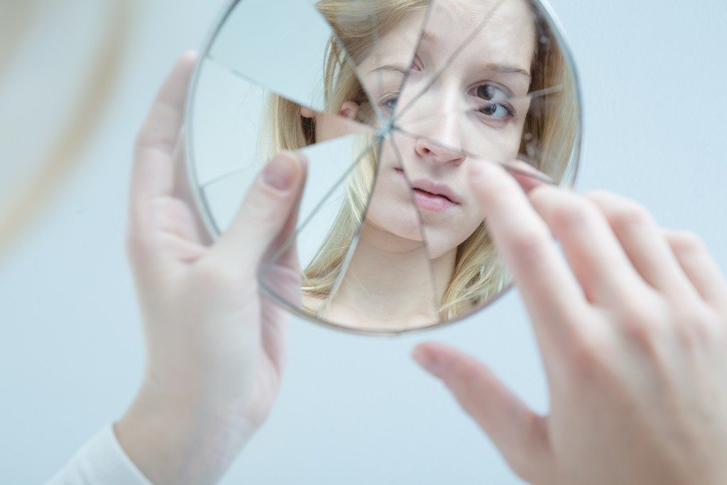 a teen looking at a broken mirror