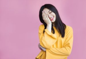 woman in a colorful top and background covering her face while smiling