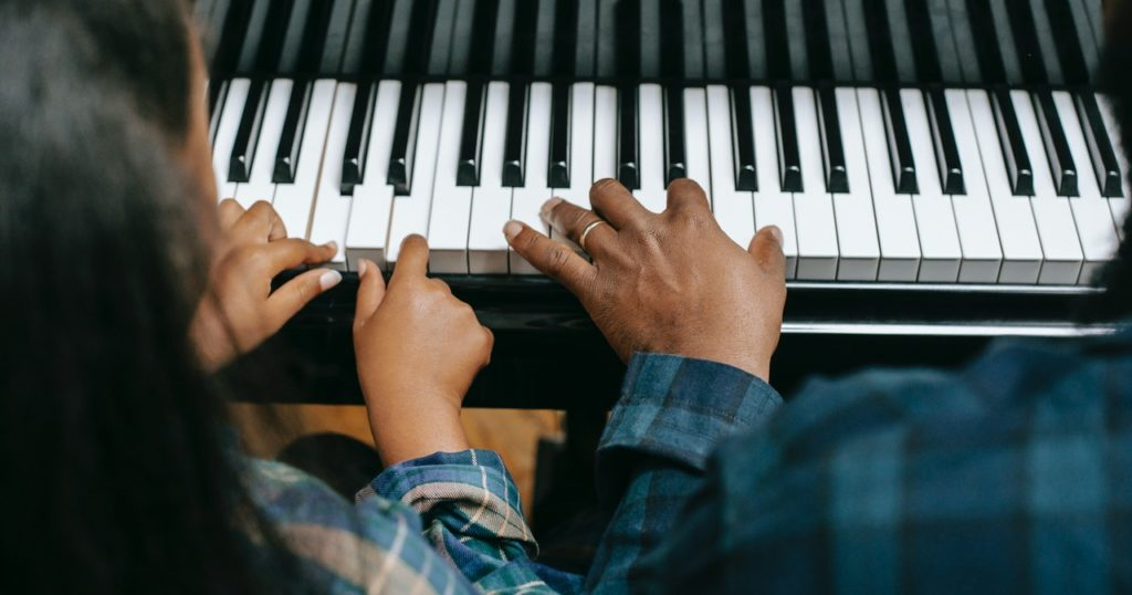 kid taking piano lessons